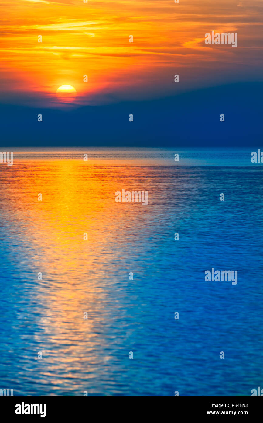 Natural spectacle - colorful blue and orange reflecting sunset at sea horizon (copy space) - Stock Image
