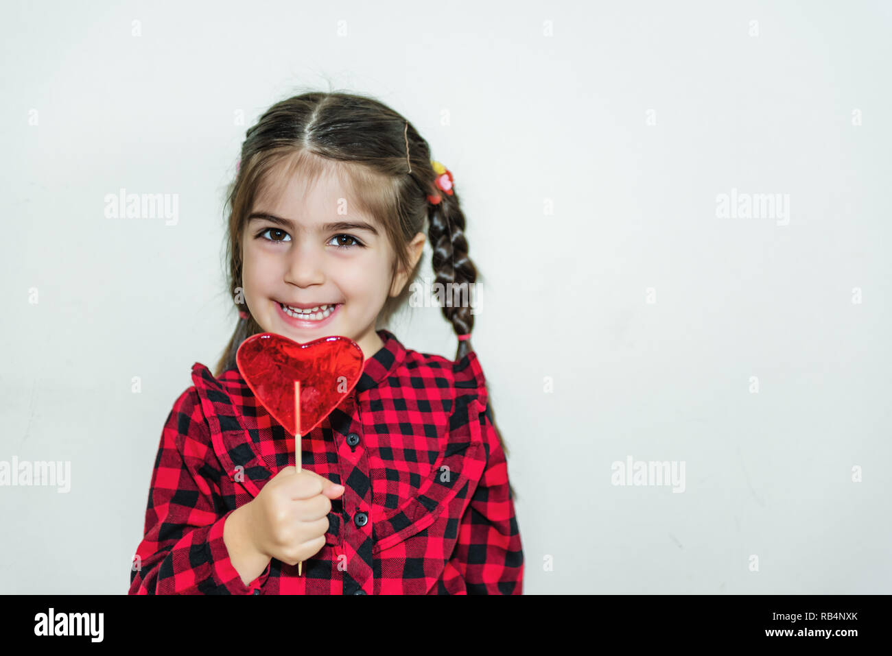 2227315850a25 Adorable lovely little girl holds lollipop in heart shaped red  candy.Holiday concept with isolated
