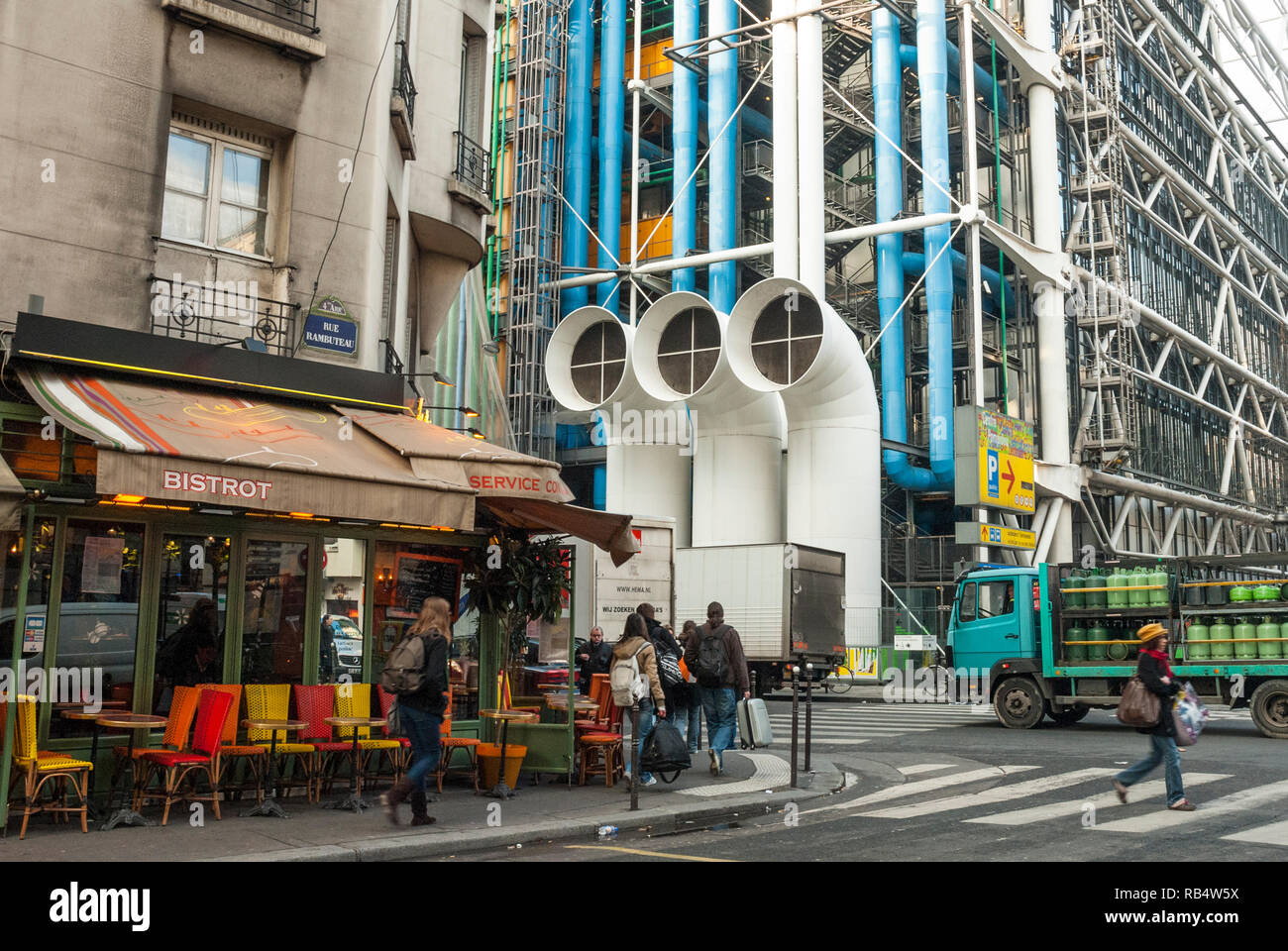 Paris street scene, winter, contrasting the old style Parisian architecture of a small cafe next to the radical architecture of the Pompidou Centre. Stock Photo