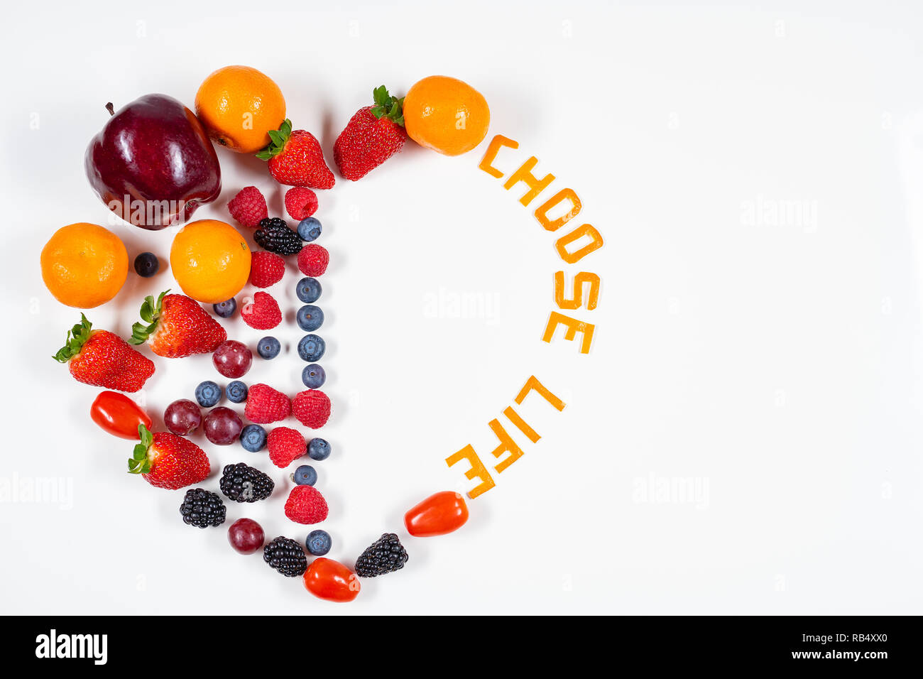 Heart shaped fruit arrangement using a various types of fruit with a message reading Choose Life made out of tangerine peels. - Stock Image