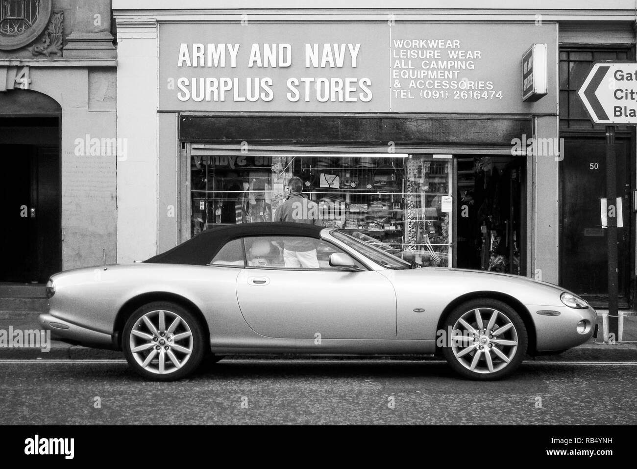 A man standing behind a Jaguar sports car parked outside an Army and Navy Surplus shop in Newcastle upon Tyne, Tyne and Wear, UK - Stock Image