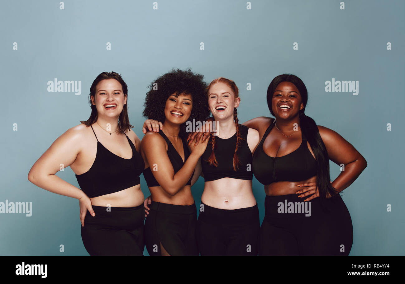 7216201588 Portrait of group of women posing together in sportswear against a gray  background. Multiracial females
