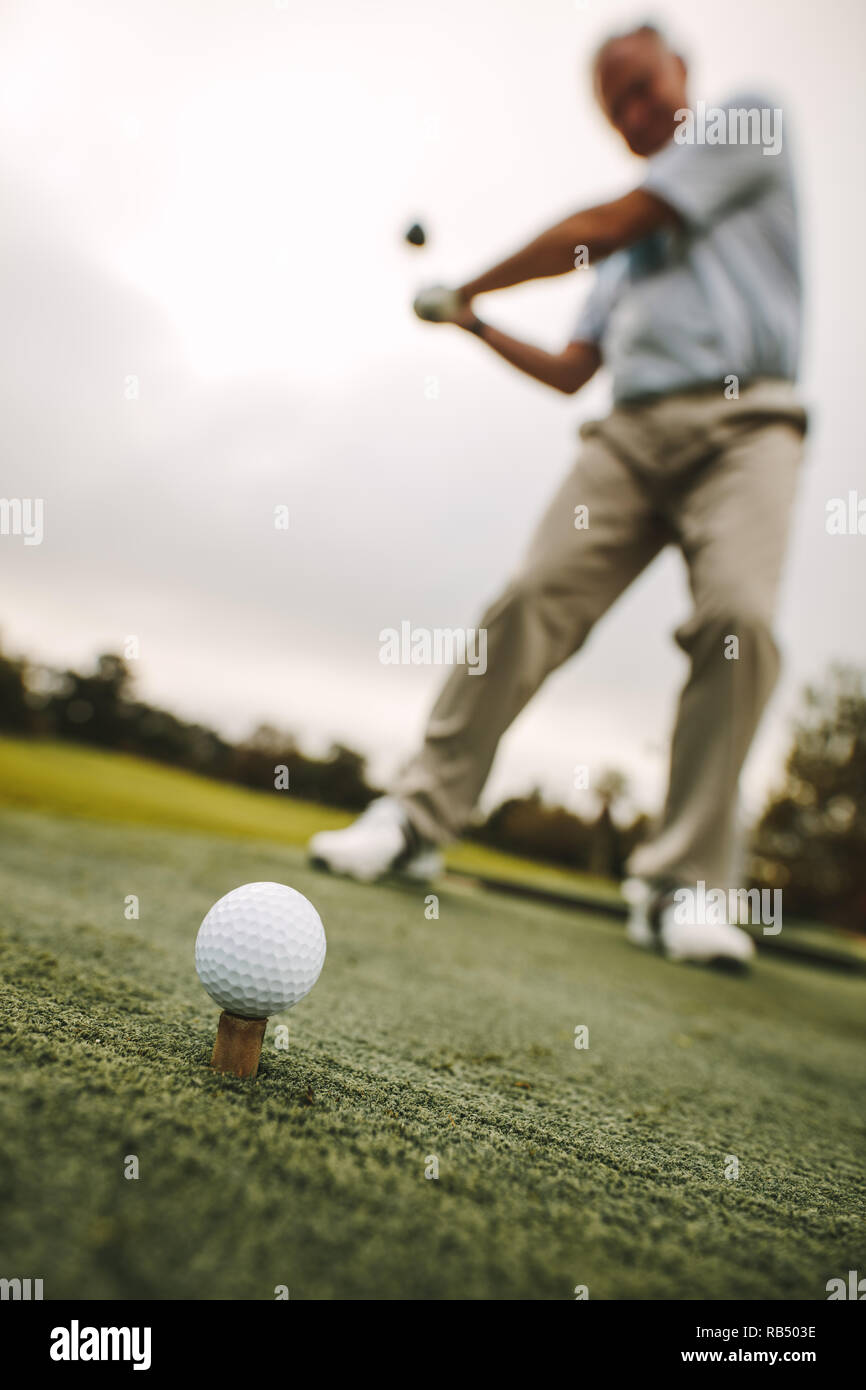 Golf ball on tee with male player practising a shot at driving range. Focus on golf ball on tee with golfer taking a shot. - Stock Image