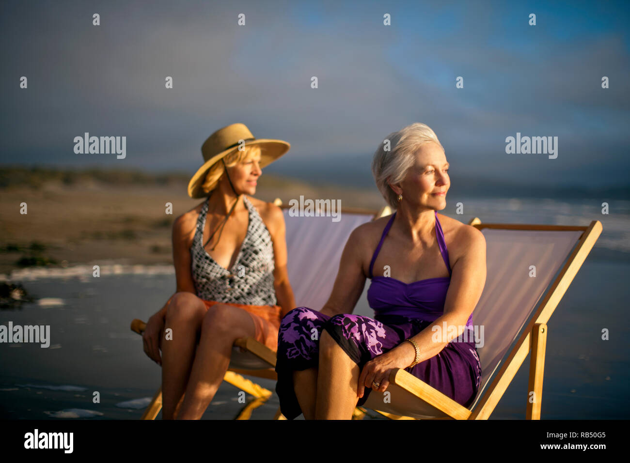Mature woman and friend in swimsuits on beach stock photos