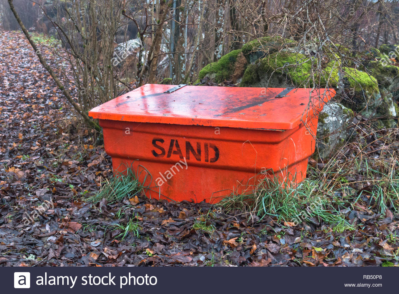 red box of sand to scatter in the case of black ice - Stock Image