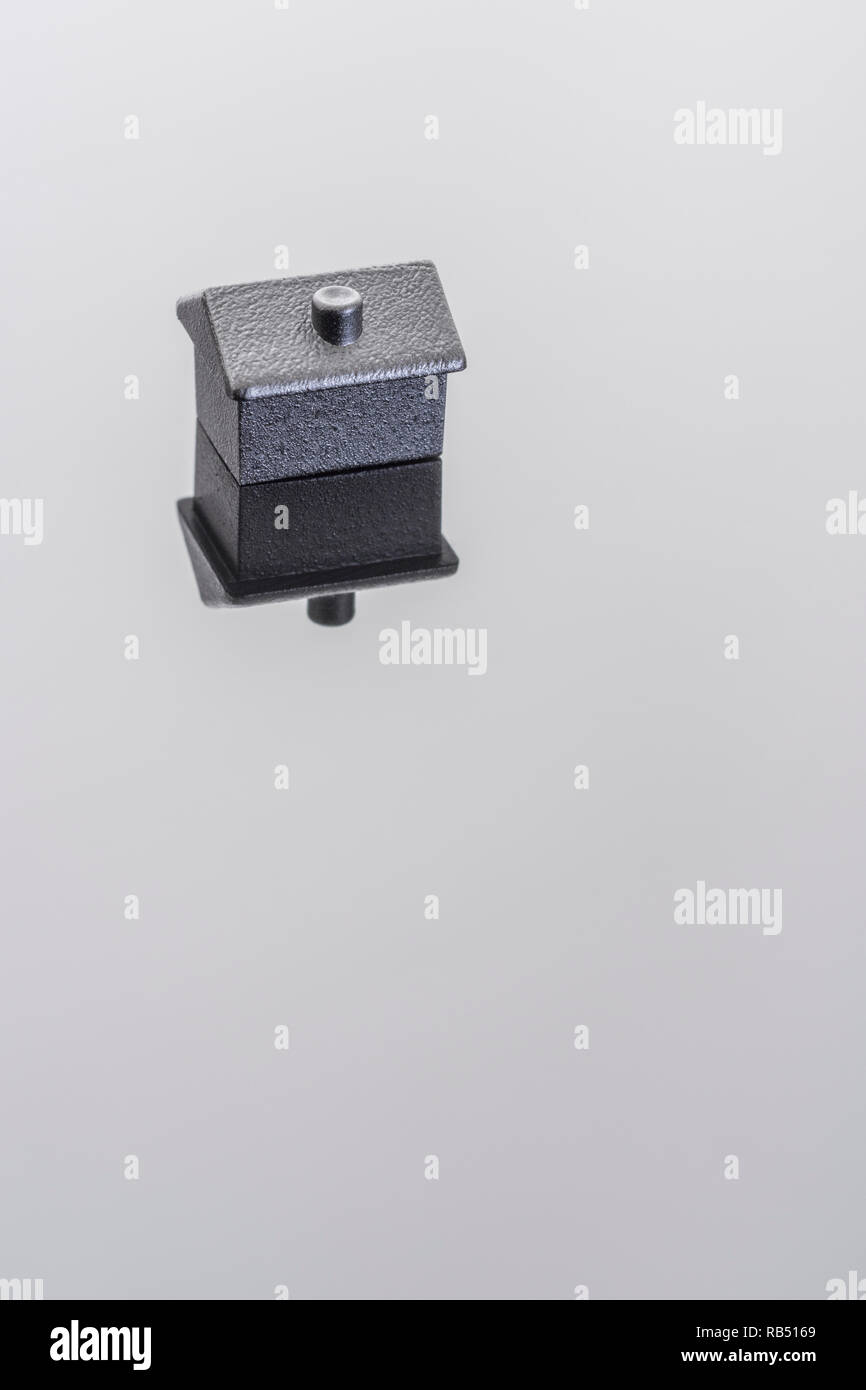 Painted toy black house on shiny background. Metaphor mortgages, rentals, rent arrears, repossessions, finding a home, property ladder, Housing Crisis - Stock Image