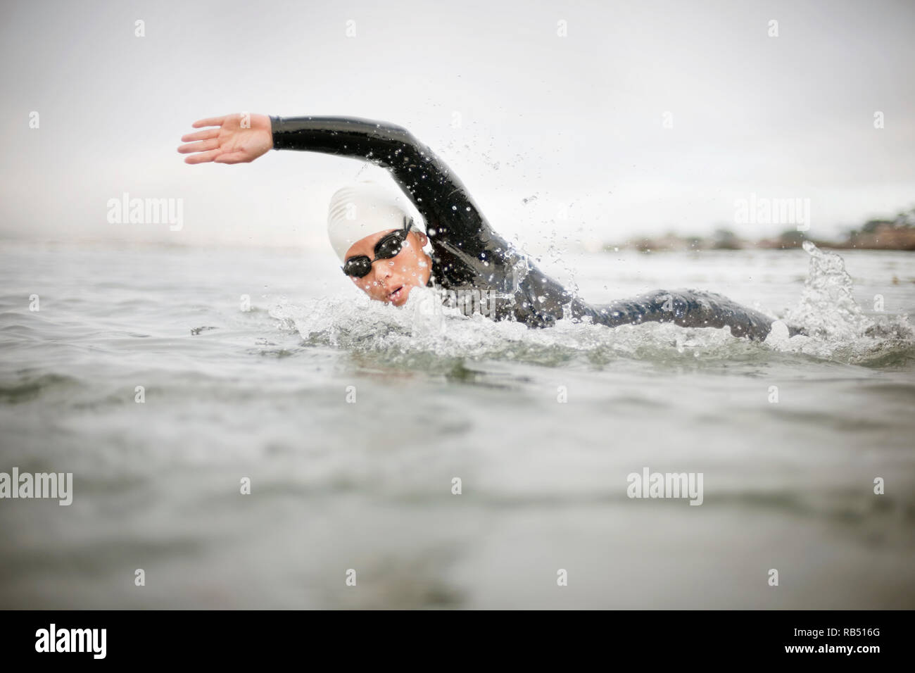 Young woman wearing a swimming cap, swimming goggles and a wetsuit swims freestyle in the open water of the sea. - Stock Image