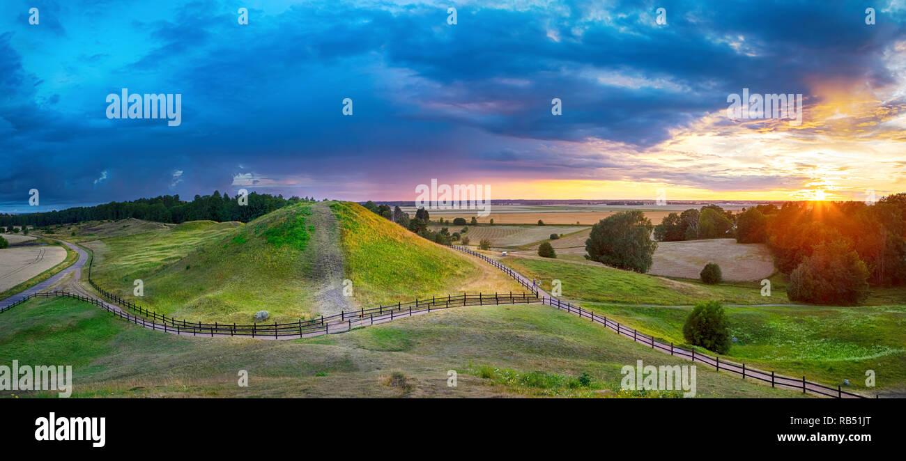 Sunset over Royal Mounds in Gamla Uppsala, Uppland, Sweden (HDR pnorama) - Stock Image