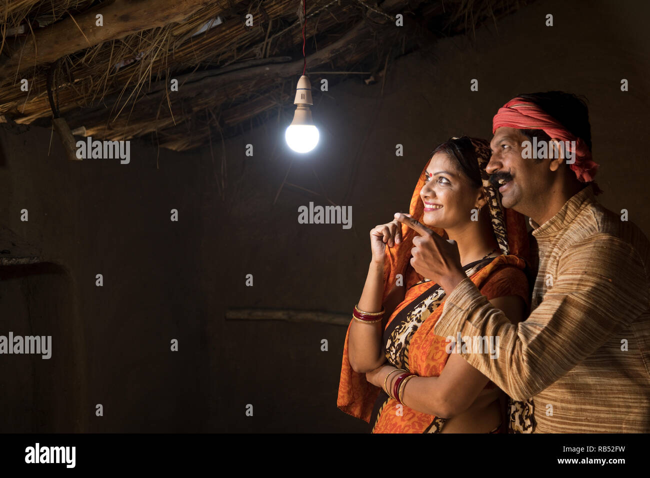 Rural Indian couple delighted at the glow of light bulb and electricity reaching their home after long wait - Stock Image