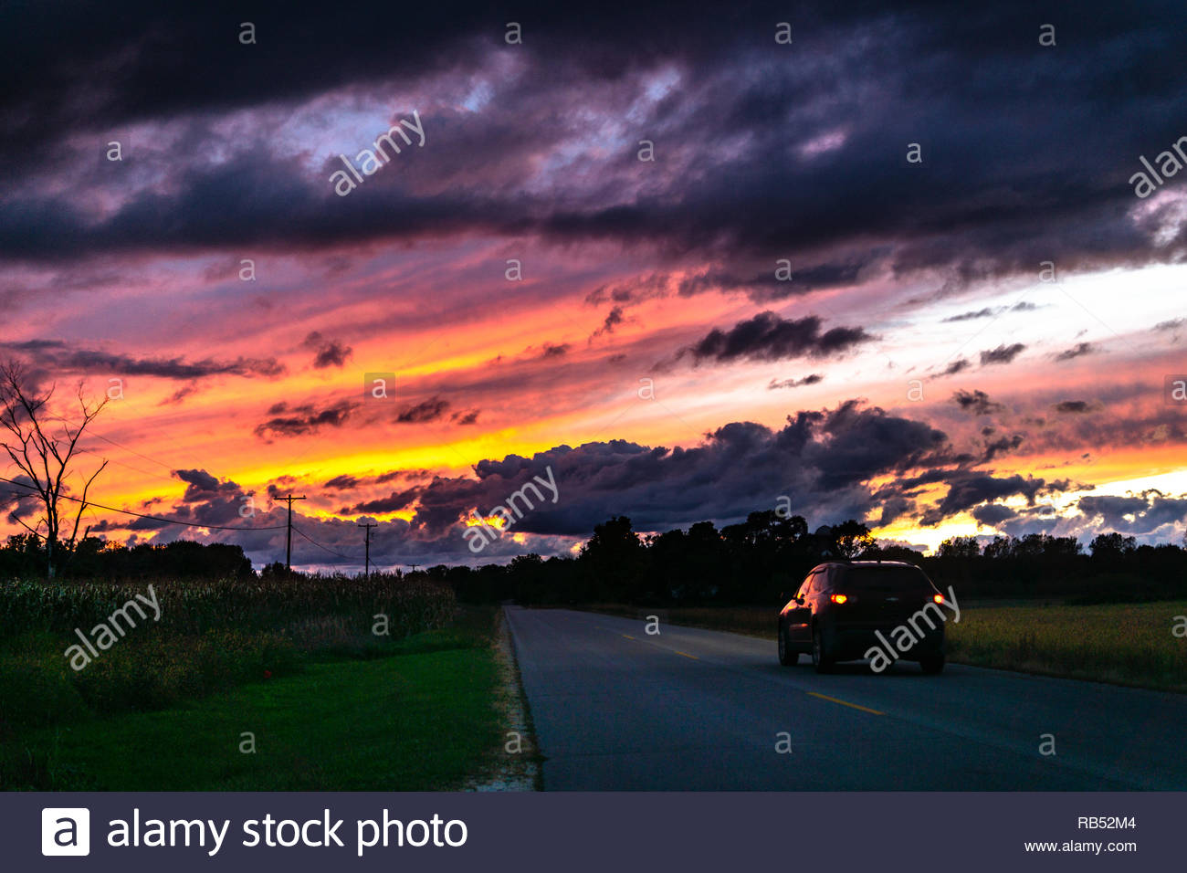 Black car driving into the sunset on a country road with the color reflecting off the paint and windows - Stock Image