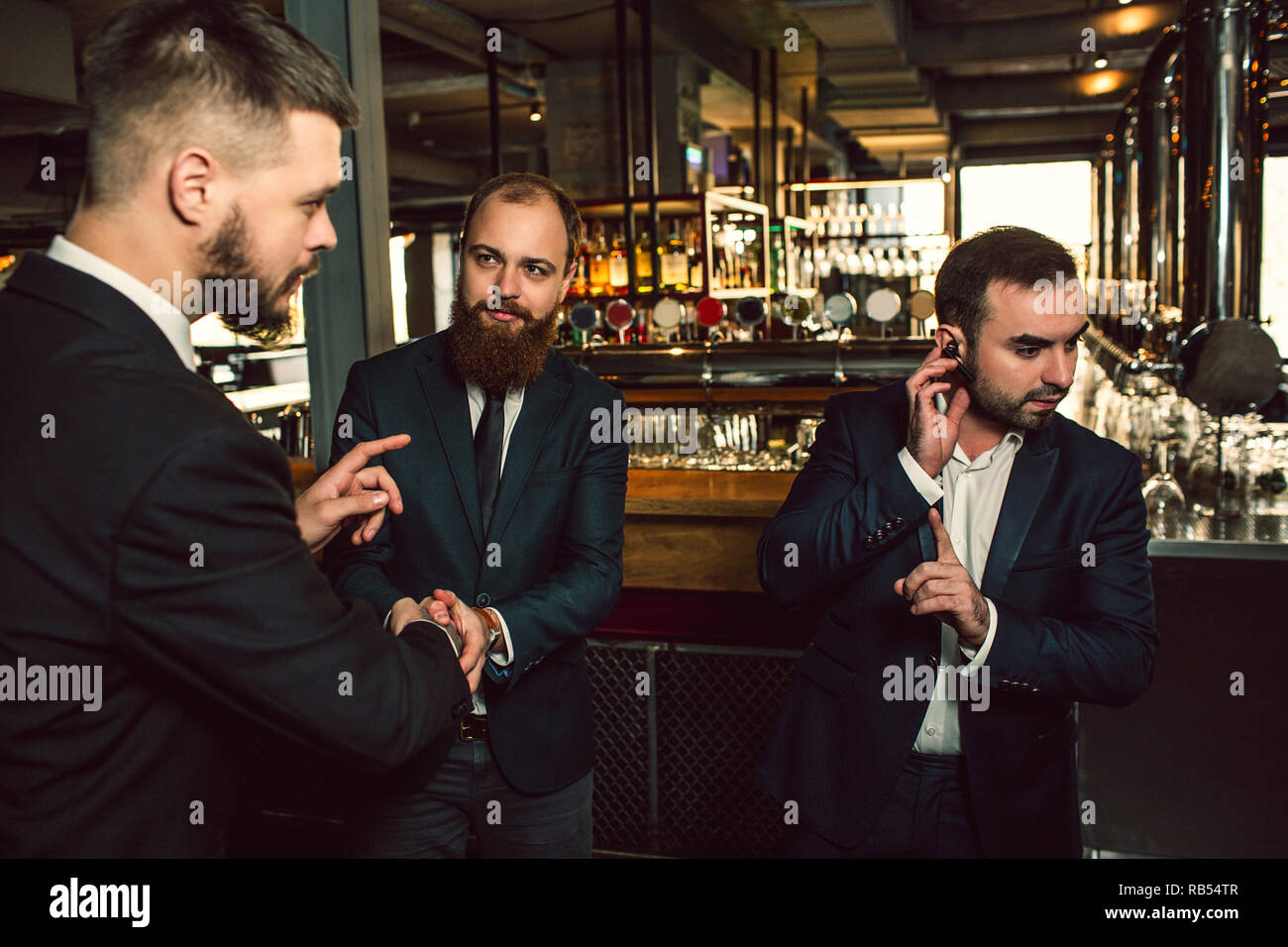 Three young men stand in pub. One hold hand on headphone. He show finger up. Second young man look at first and try to toalk. Third guy look at second one. - Stock Image
