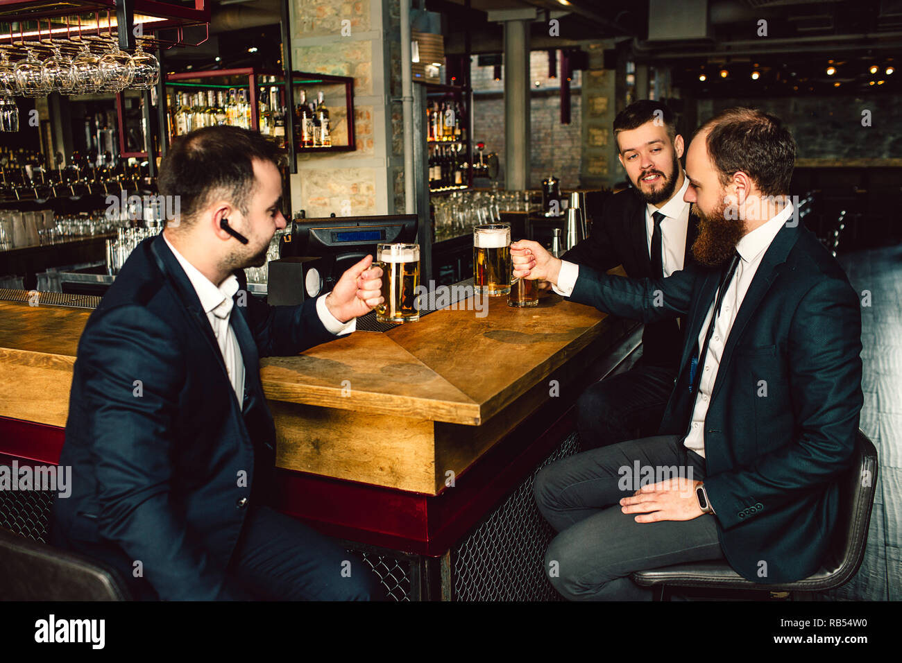 Three young businessman sit at table and hold cips of beer. They talk. People wear suits. First guy has black headphone in ear. - Stock Image
