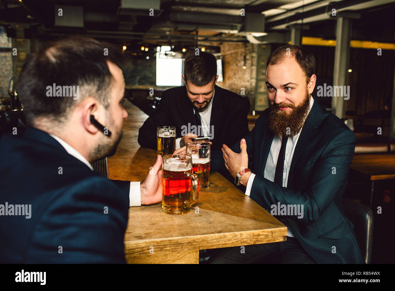 Positive young bsinessmen in suits sit together at table. They hold mugs of beer. Guy in front has balck headphone in ear. Men are in bar. - Stock Image