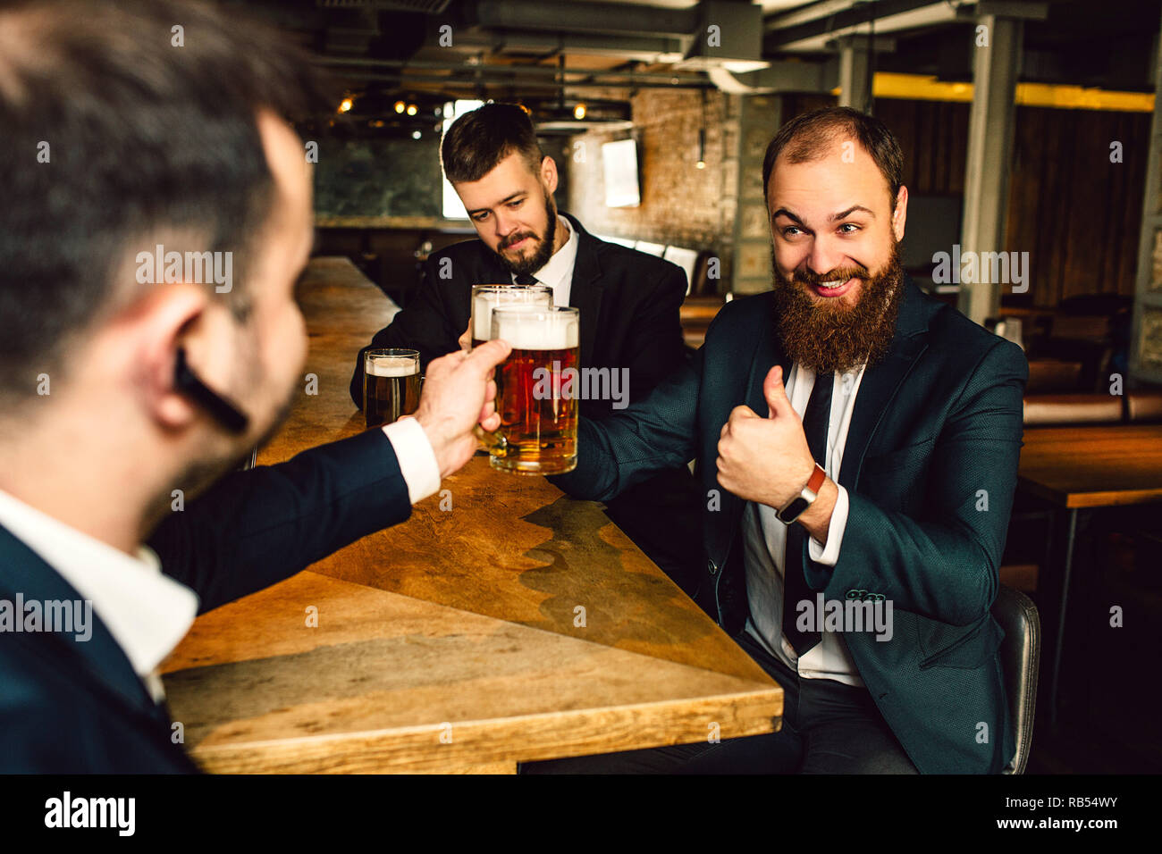Cheerful young businessmen sit at table. They hold mugs of bear. Bearded guy hold big thumb up. Stock Photo