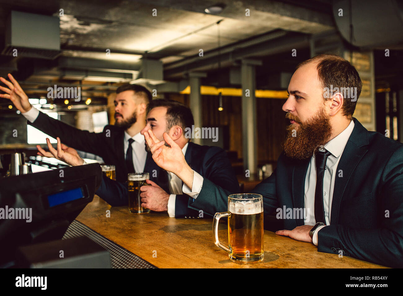 Young men in suits sit in bar and cheer. They watch TV. Guys are emotional. They wave and reach hands forward. - Stock Image