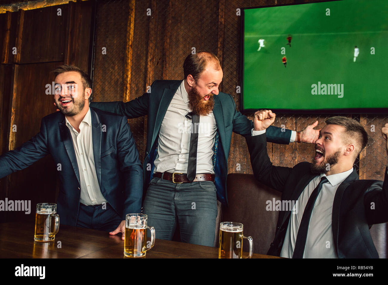 Excited young man cheer in pub. They look at each other and wave with hands. Guys watch football game. - Stock Image