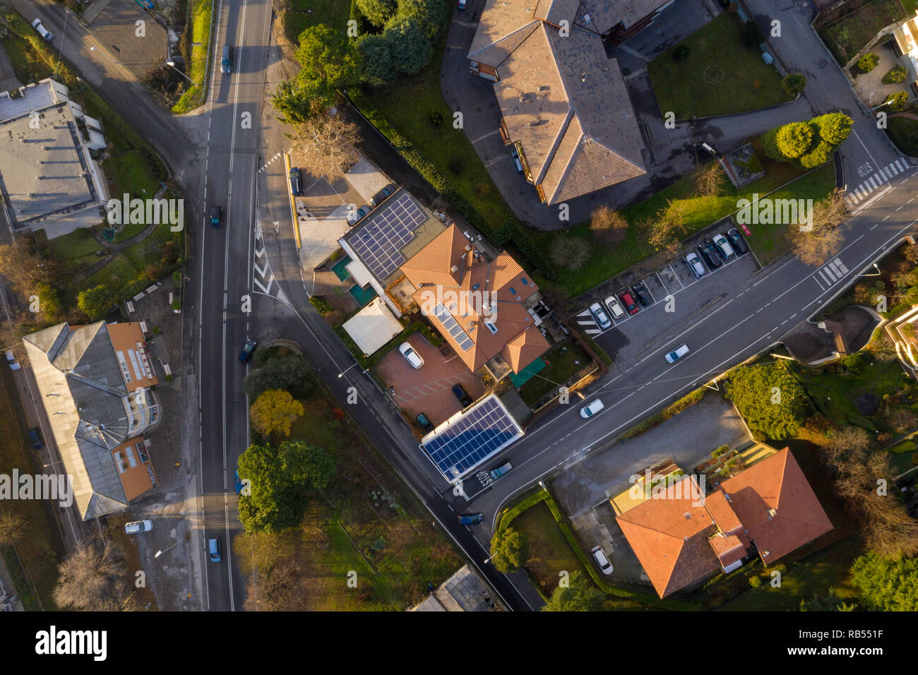 from above, houses in europe, two roads with trees, day sunrise few buildings - Stock Image