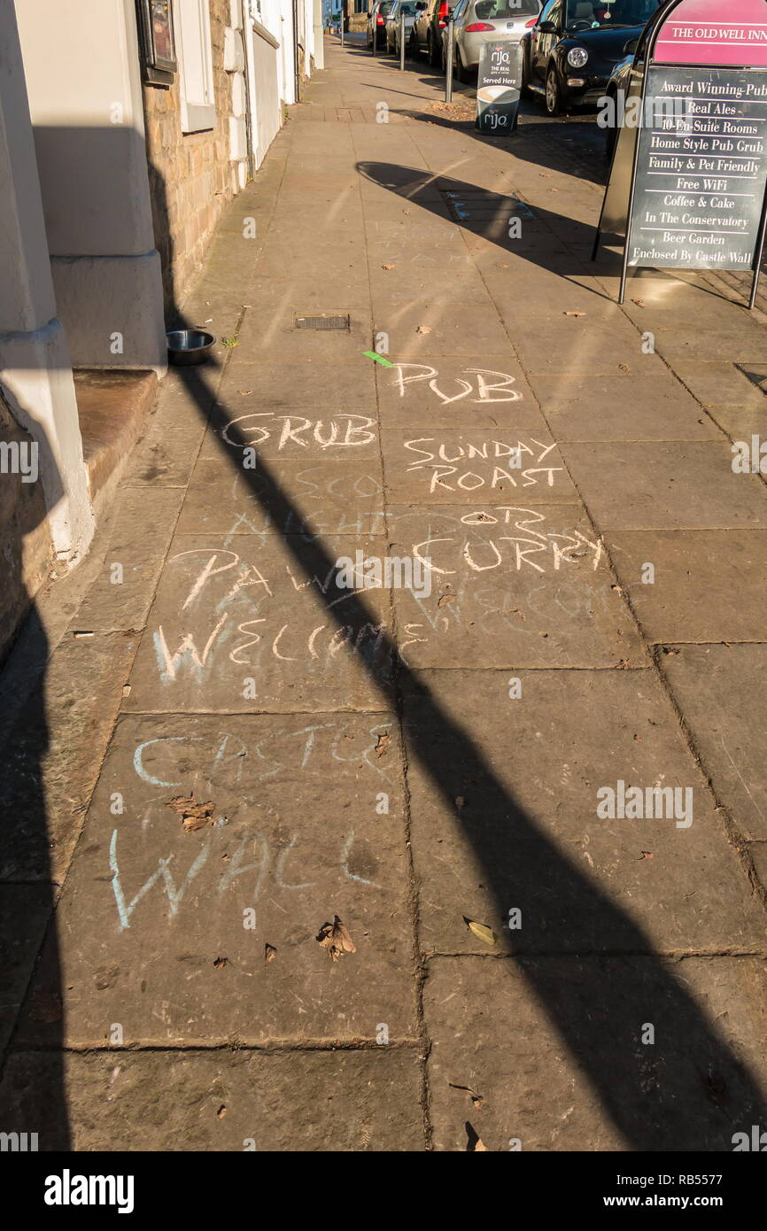 Pavement graffiti advertizing a pub's Sunday food menu - Stock Image