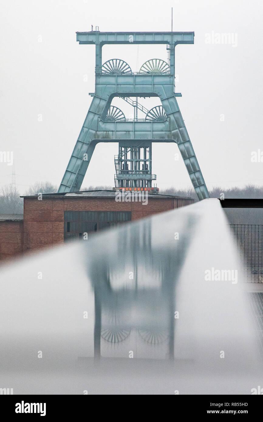 Der Förderturm der Zeche Ewald spiegelt sich in einem Geländer. Stock Photo