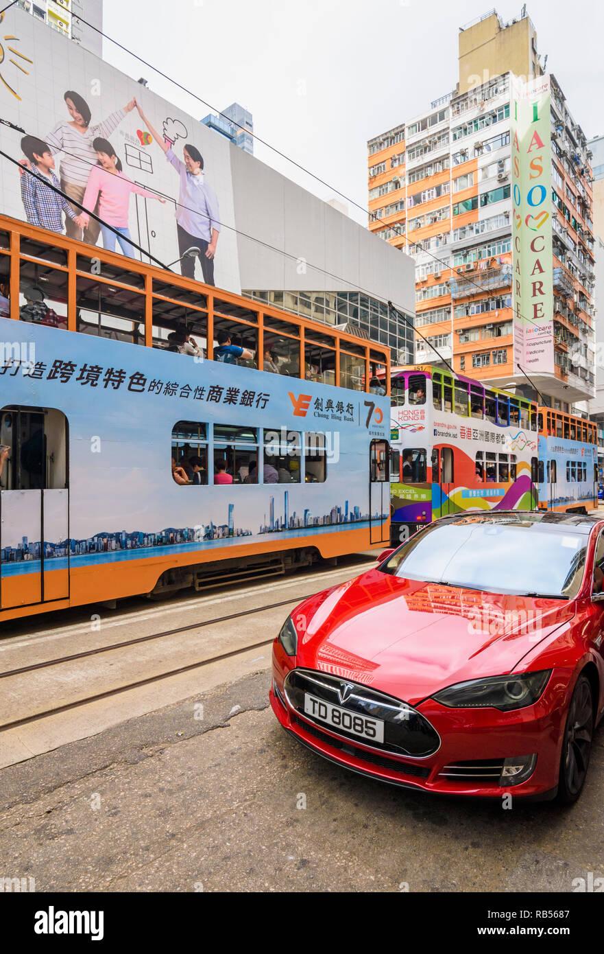 Tesla and trams on Johnston Rd, Wan Chai, Hong Kong - Stock Image