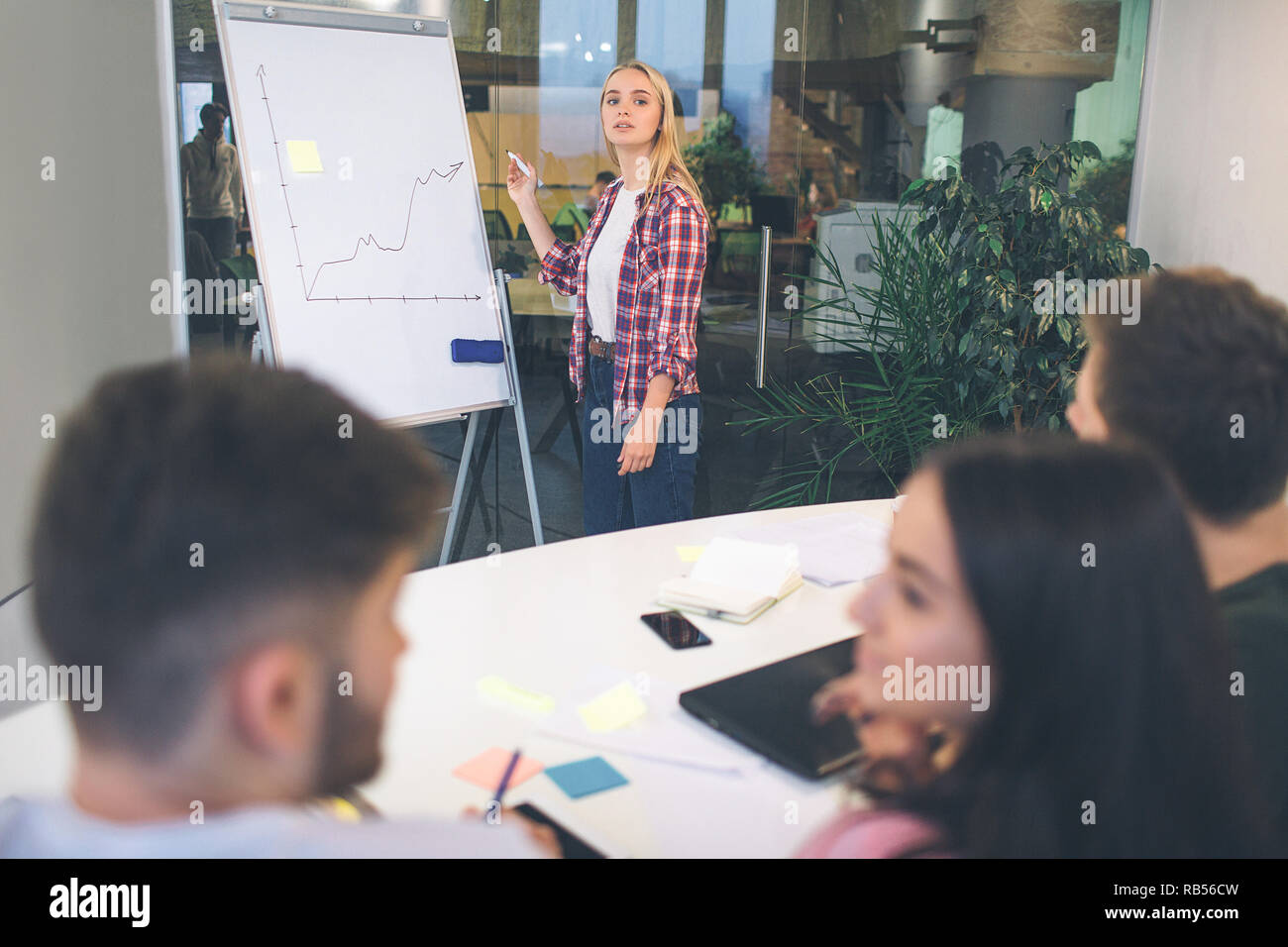 Nice young blonde woman look on camerea. She stand at flipchart and draw grafic line. Another people have conversation between themselves. Stock Photo