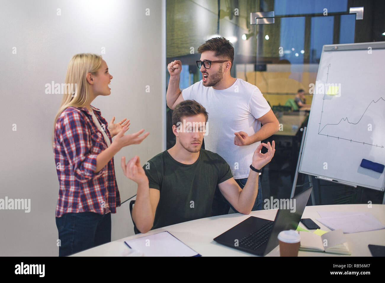 Young bearded man and blonde woamn argue with each other. They stand behind guy who meditates. He keep eyes closed and concentrated. - Stock Image