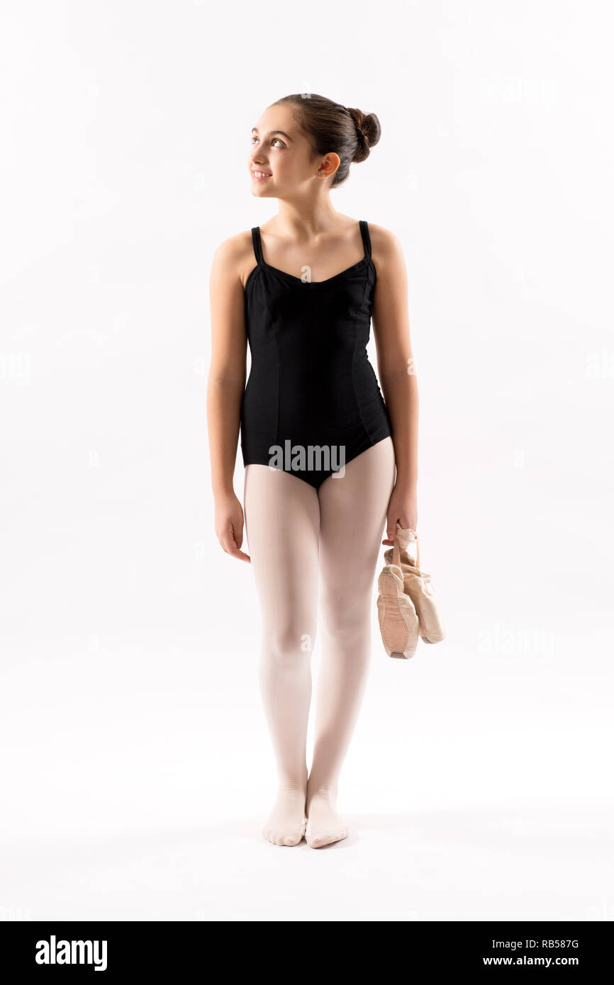 Relaxed happy attractive young ballerina in a leotard standing holding her shoes looking aside with a smile over white - Stock Image