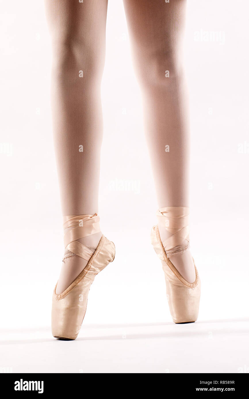 e153c6573f3f0 Legs of a young ballerina on pointe balancing on the tips of her toes in a  pair of pink ballet shoes isolated on white