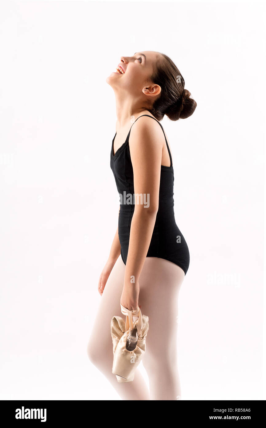 Happy young ballerina carrying her pink ballet shoes looking up laughing with her head tilted back in a close up side view on white - Stock Image