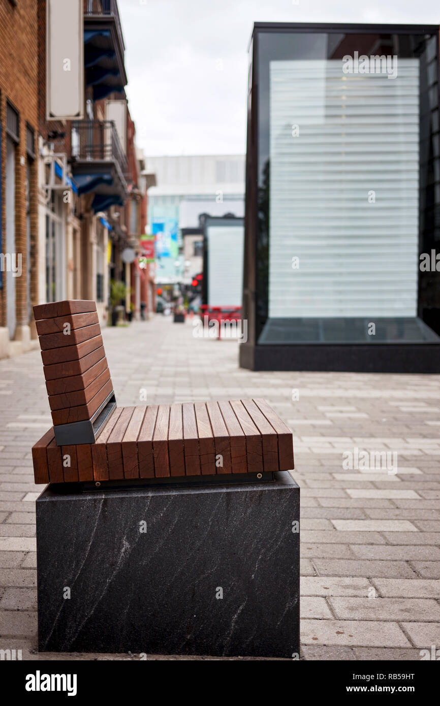 Modern brown wooden bench and empty billboard on the sidewalk - Stock Image