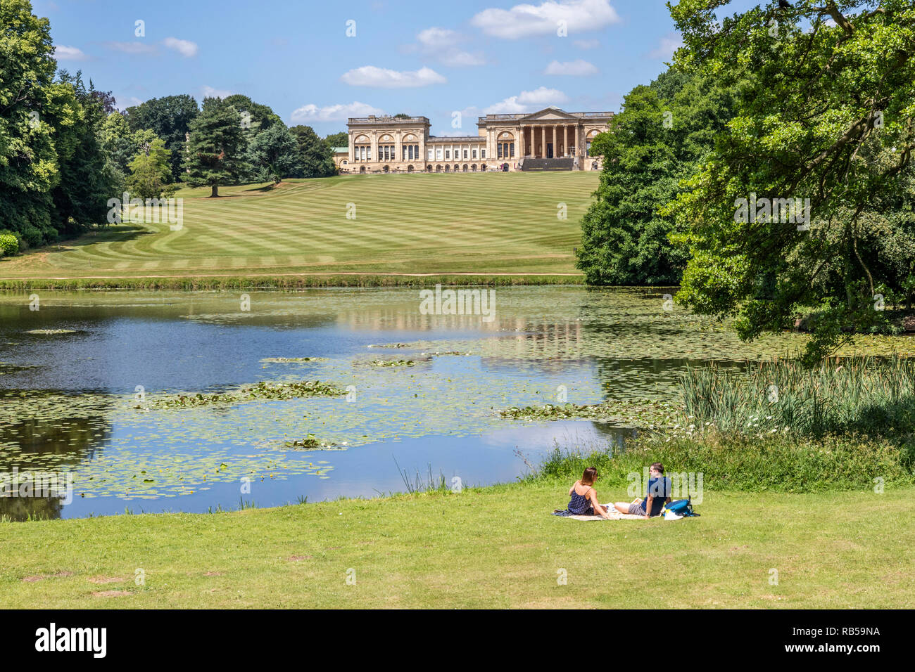 A young couple enjoying a picnic beside the lake at Stowe House Gardens, Buckinghamshire UK - Stock Image