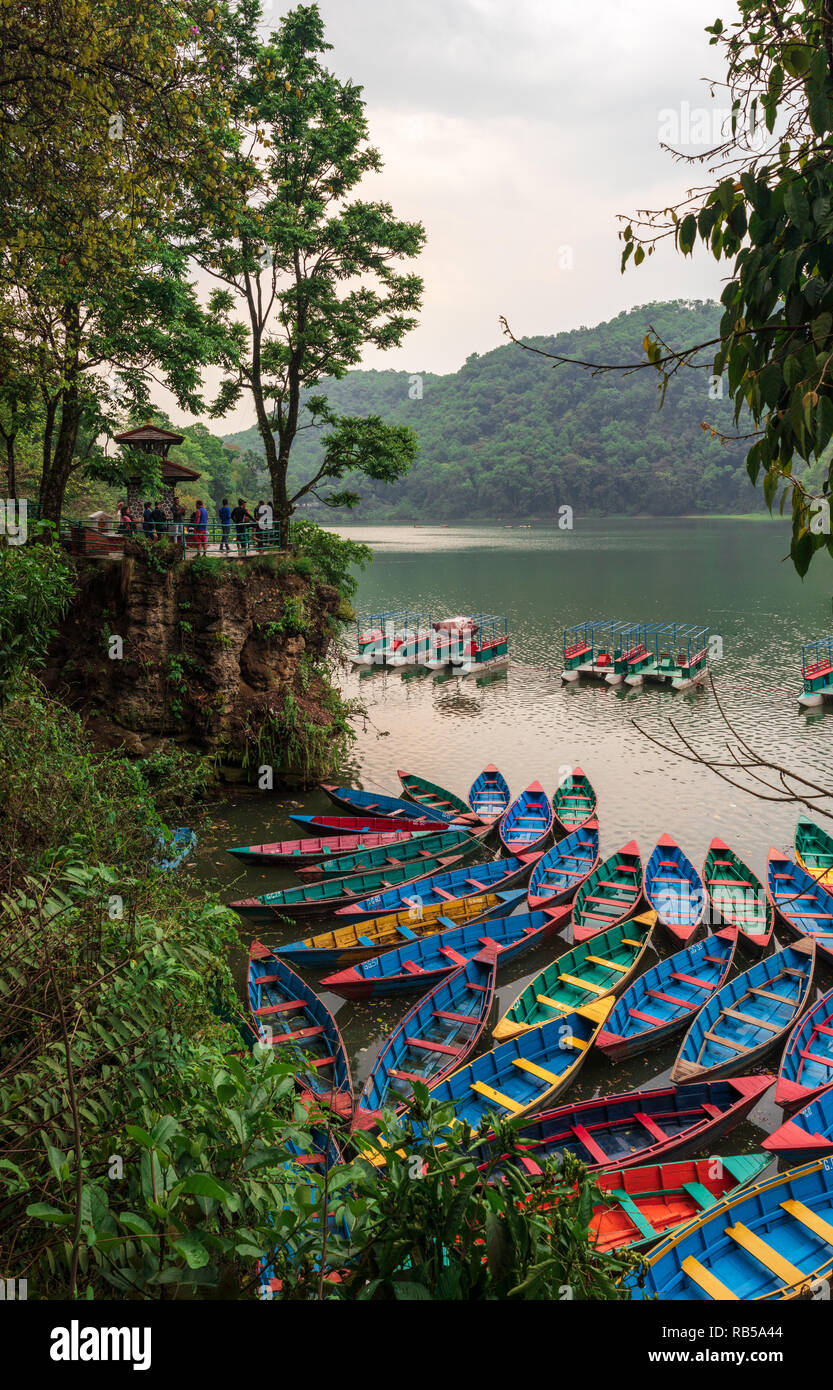 Tourists looking at the colorful boats in Pokhara lake in Nepal. - Stock Image