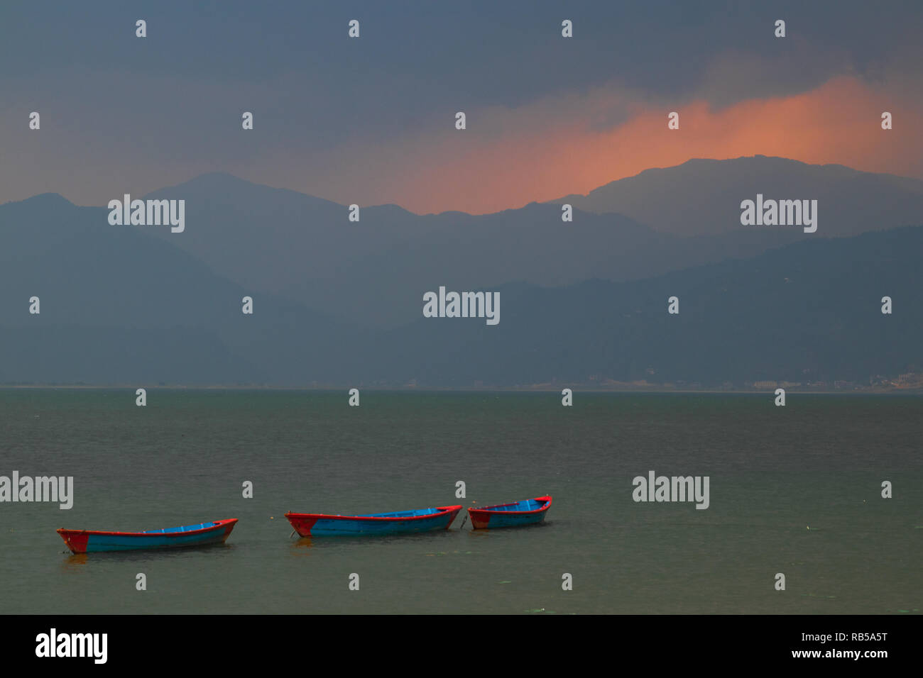 Colorful boats in Pokhara lake in Nepal during a sunset in a rainstorm Sky suddenly opening up and painting the mountains in the background with light - Stock Image