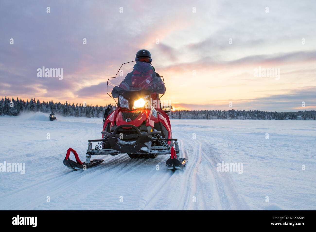 Person driving a snowmobile at sunrise over a frozen lake in northern Sweden. Shot during a sunset tour close to the Ice Hotel. Open frozen lake. - Stock Image