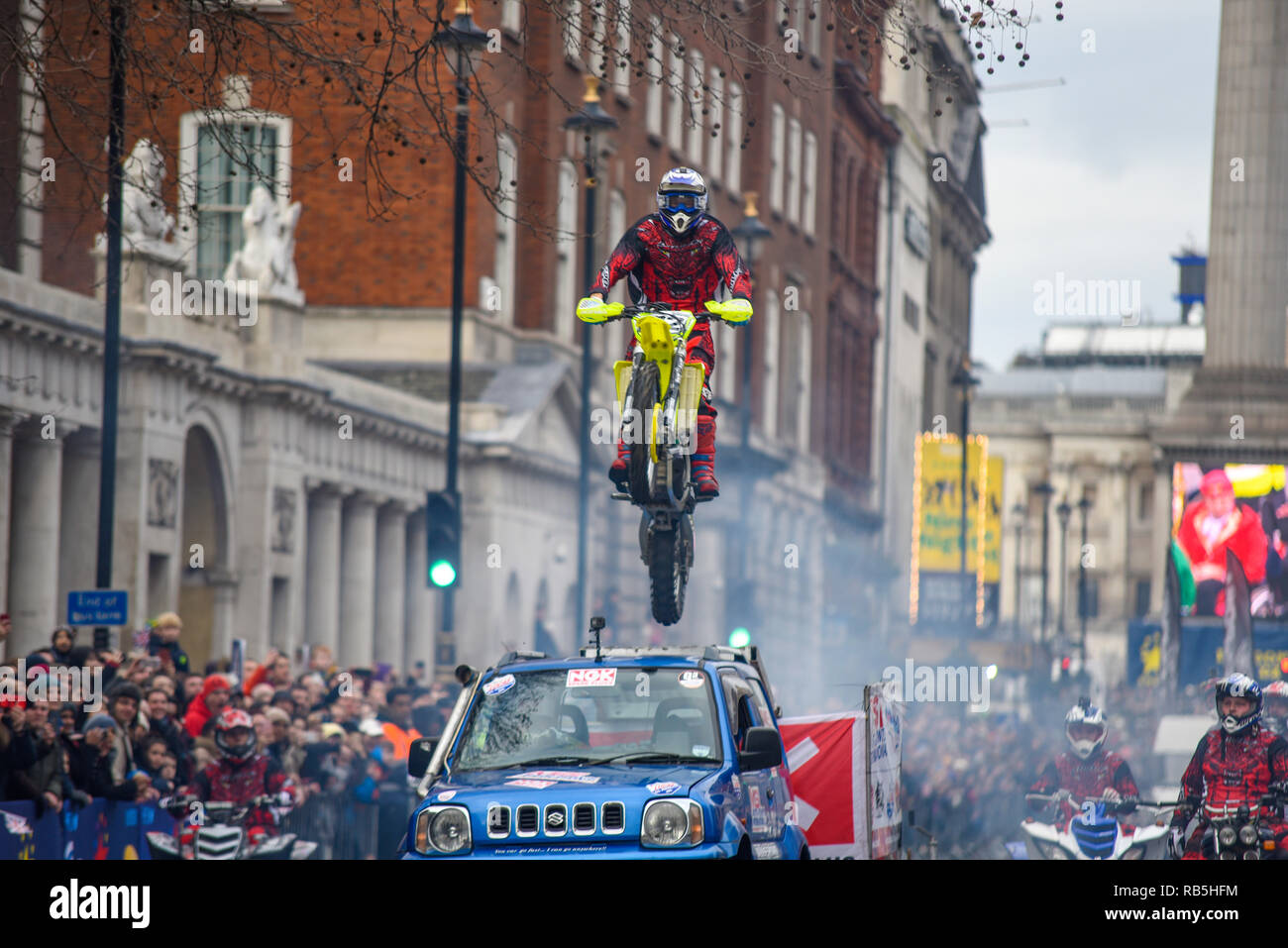 Moto Stunts International motorbike display team at London New Year's Day Parade. Motorcycle jumping over a car in Whitehall with Nelson's Column - Stock Image