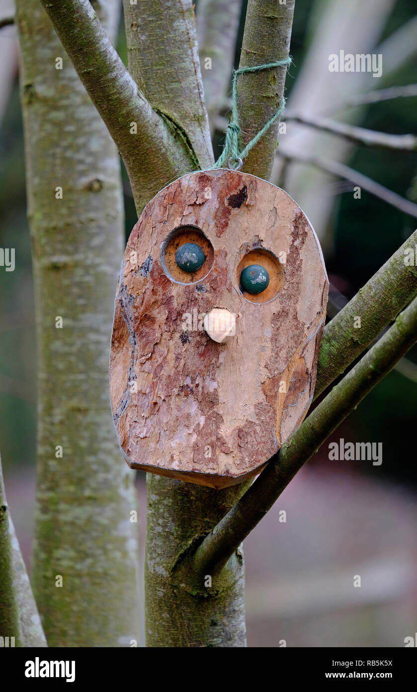 wooden face mask tied to tree in garden - Stock Image