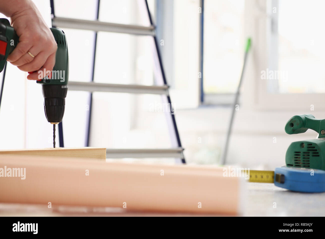 Flat drill bit make hole in wooden bar - Stock Image