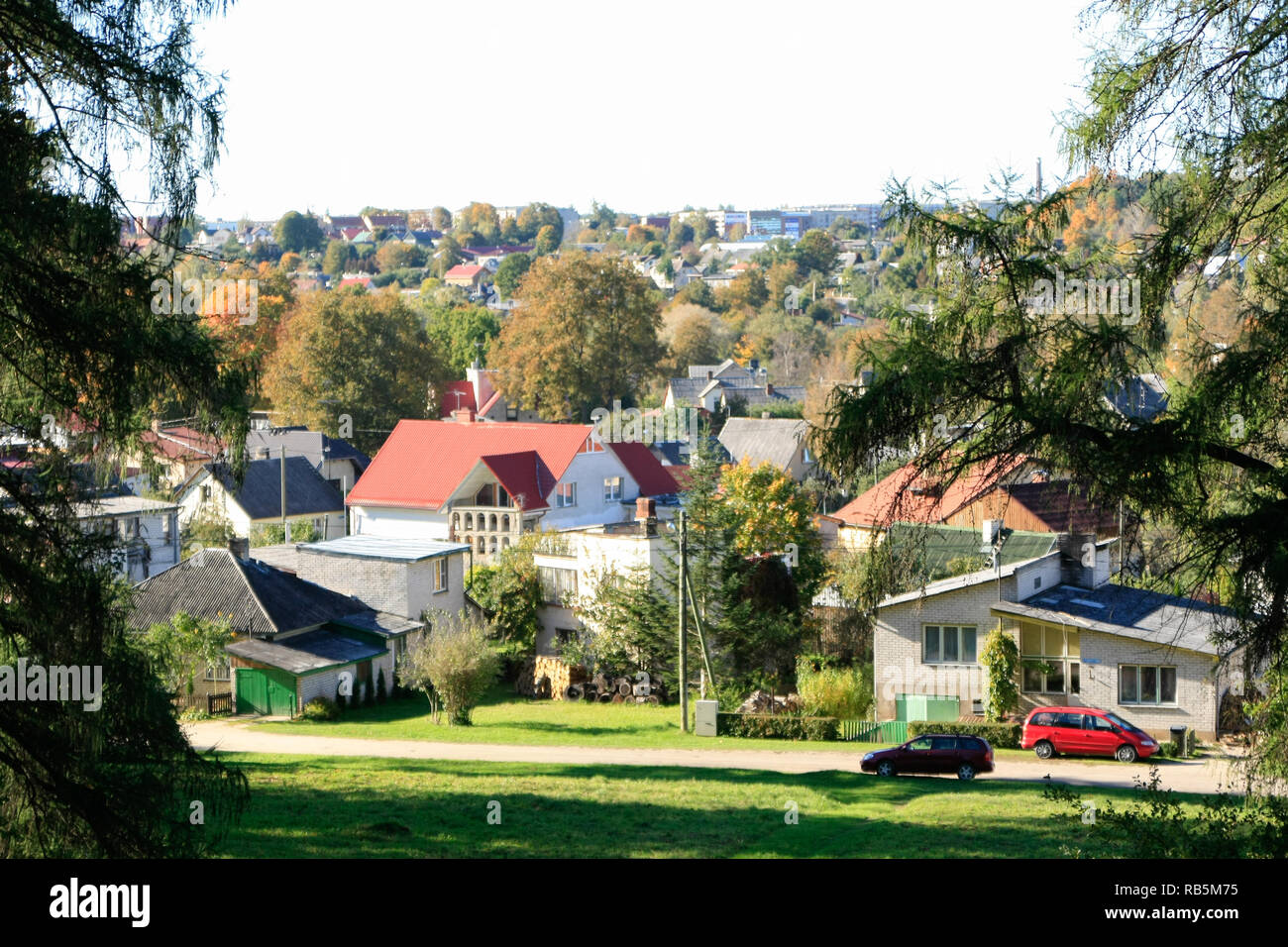 Fantastic landscape view of houses down the hill. In the background you can also see trees and forest. - Stock Image