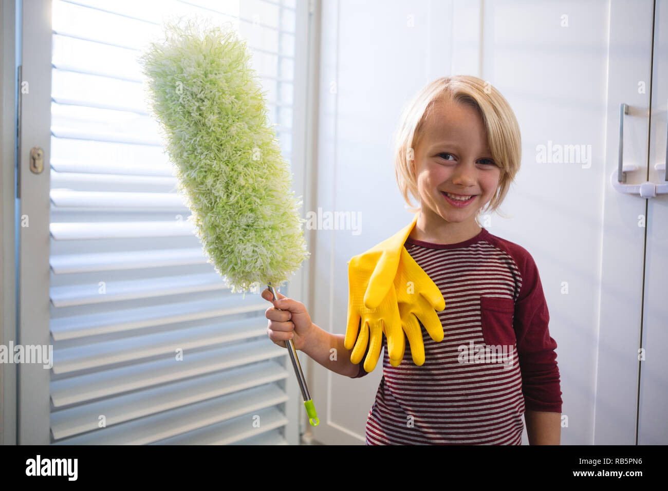 Boy holding a mop at home - Stock Image