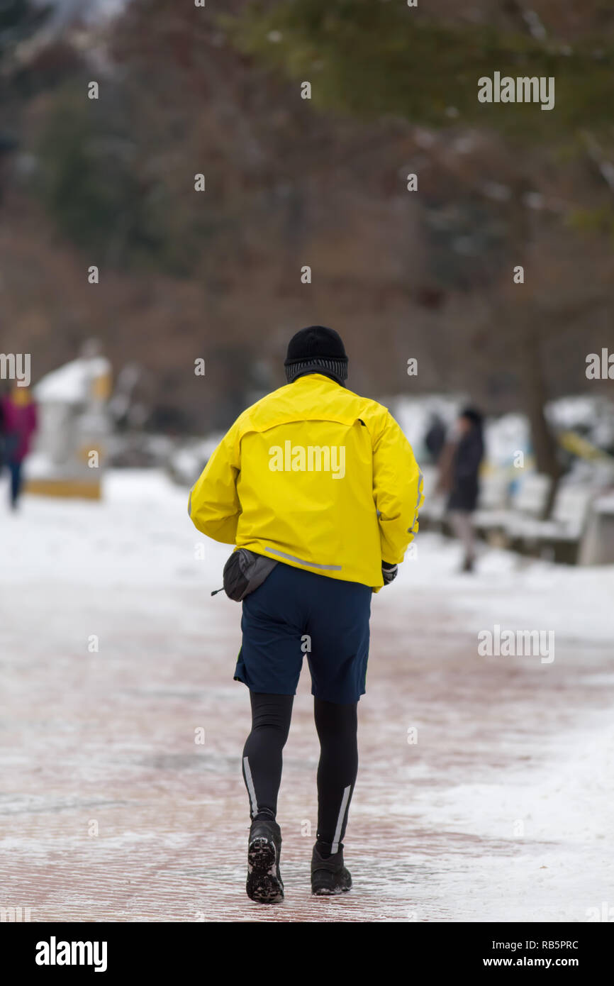 Runner with yellow sport jacket running in winter park from behind