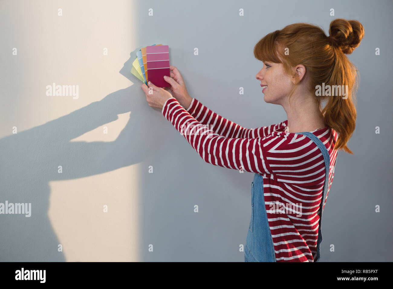 Female painter matching color shades - Stock Image