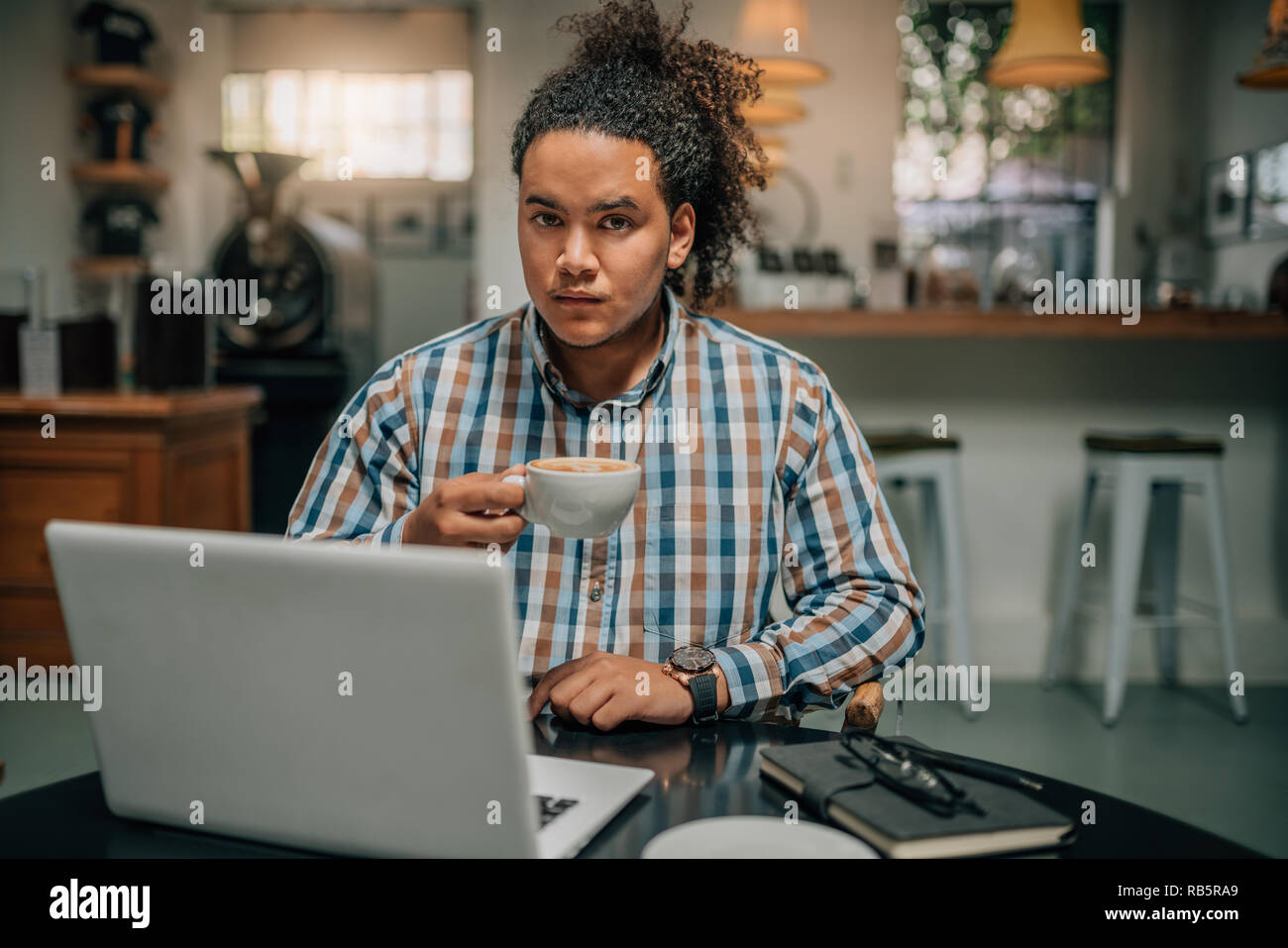 Portrait of a young handsome mixed race guy with tied up afro, holding a cup off coffee behind his laptop - Stock Image