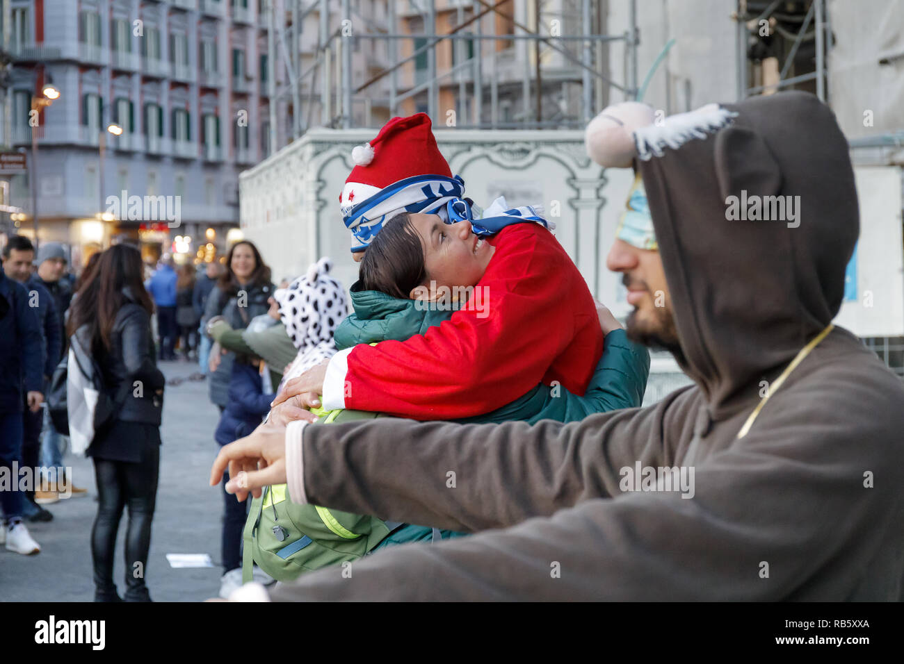 Naples, Italy - December 16, 2018: Piazza del Plebiscito, tourist hugs a Santa Claus on the street in a sign of solidarity and peace. We are in the Ch - Stock Image