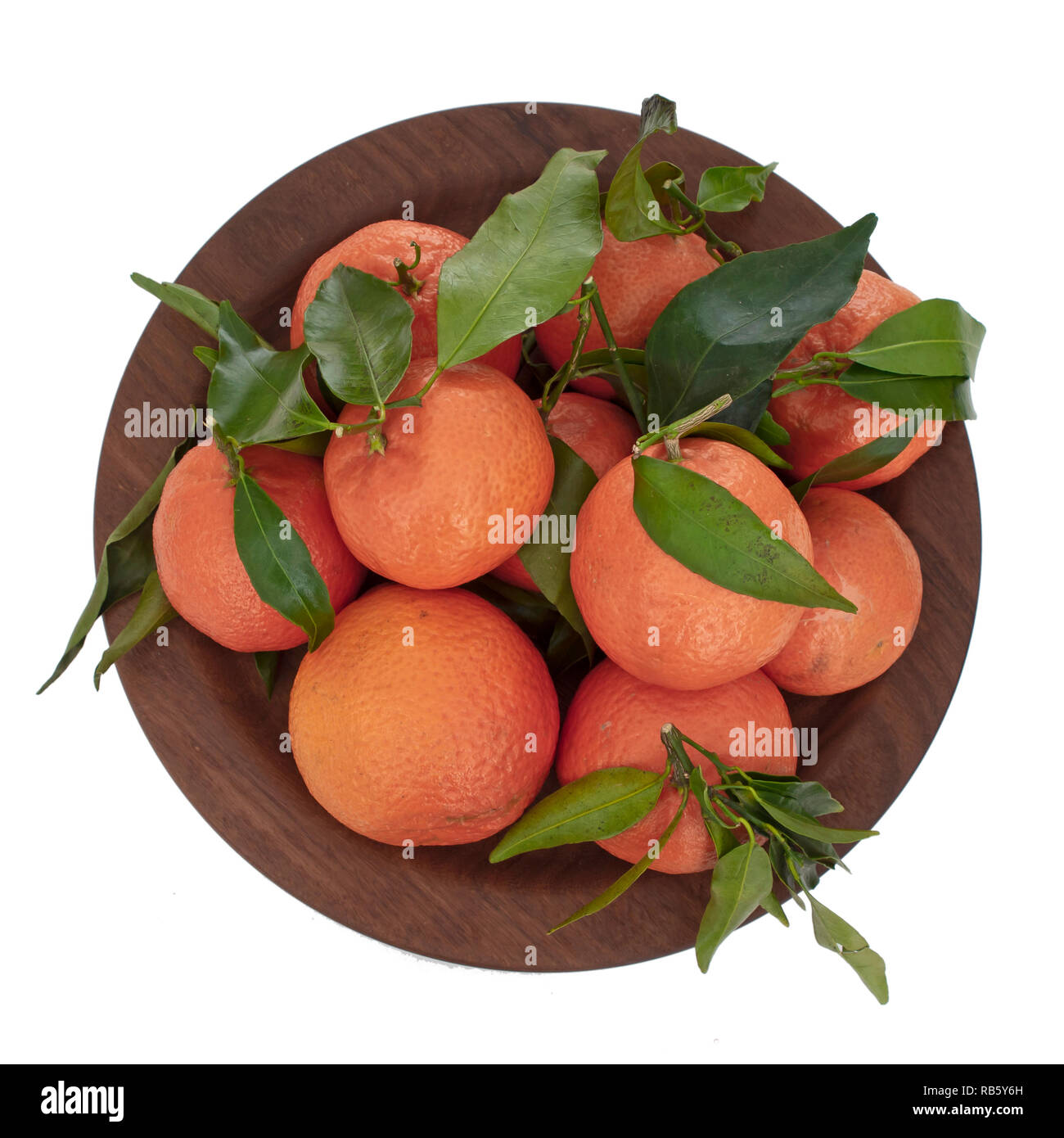 Oranges. Several ruits with leaves on plate, top view, isolated on white. - Stock Image