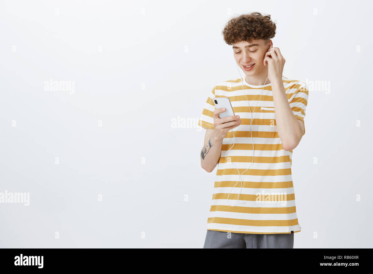 Delighted and carefree modern young man with trendy curly