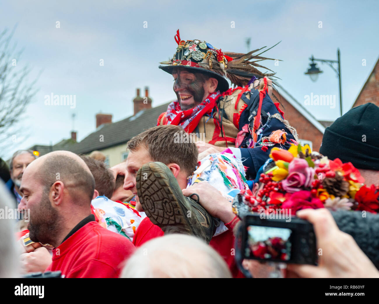 Haxey, Lincolnshire, England, UK – The Fool, with black face, carried ny The Boggins singing traditional folksongs in the ancient custom of The Haxey Hood since the 14th Century Stock Photo