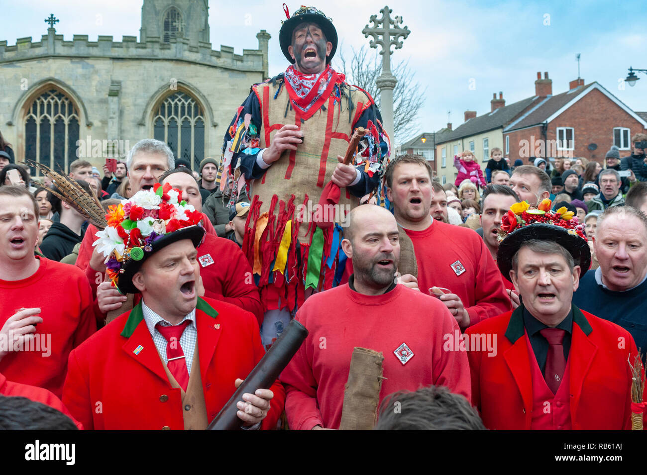 Haxey, Lincolnshire, England, UK – The Fool, with black face, and The Boggins sing traditional folksongs in the traditional ancient custom of The Haxey Hood since the 14th Century Stock Photo