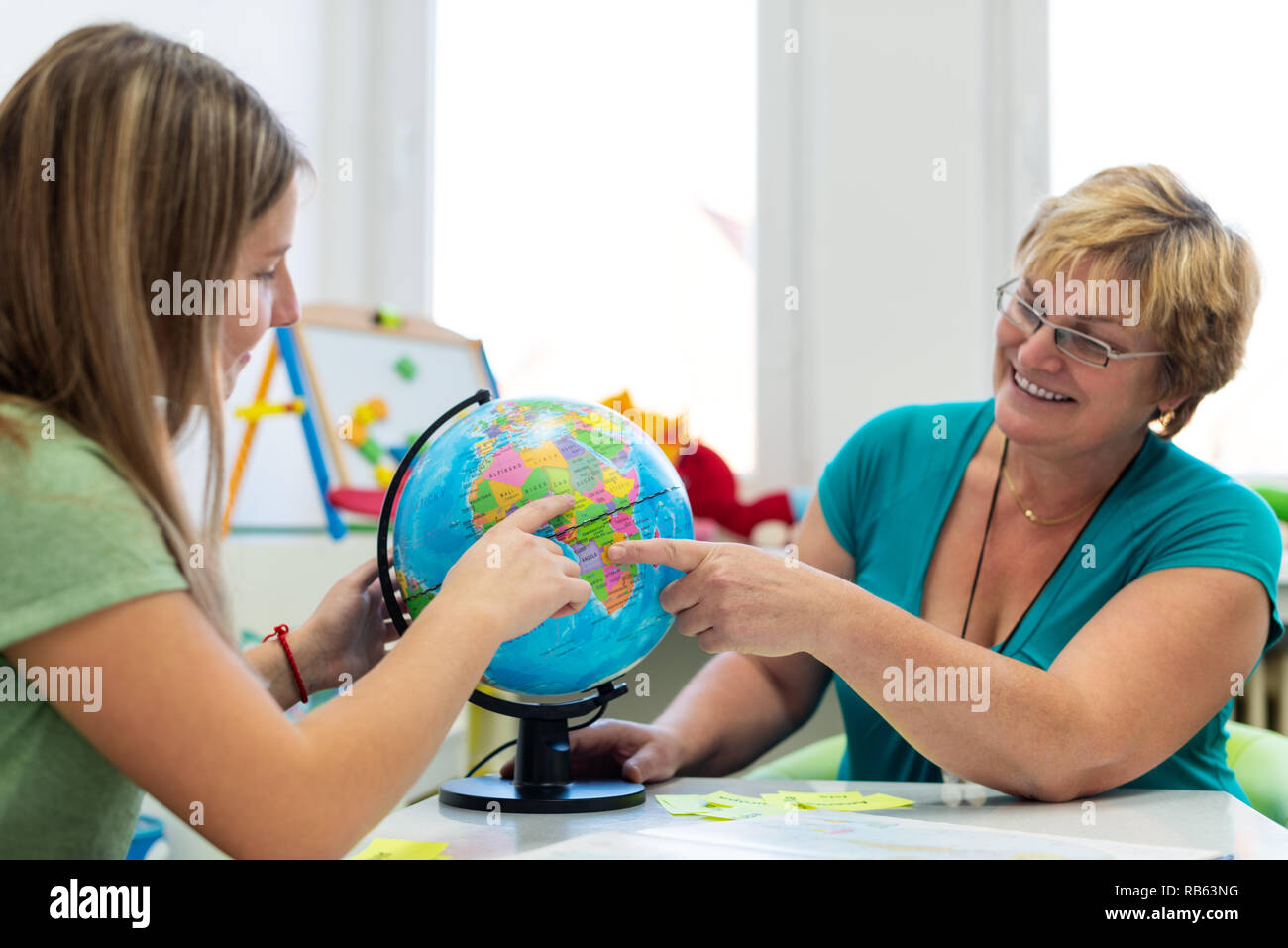 Therapist working with a teenage girl with learning difficulties. Private geography tutoring session. Teacher with teenage student in class pointing t - Stock Image