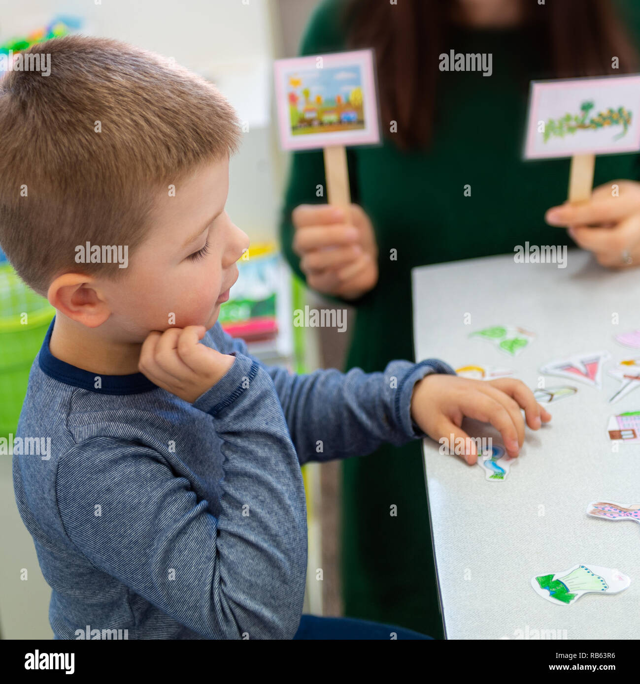 Young boy in speech therapy office. Preschooler exercising correct pronunciation with speech therapist. Child Occupational Therapy Session. - Stock Image