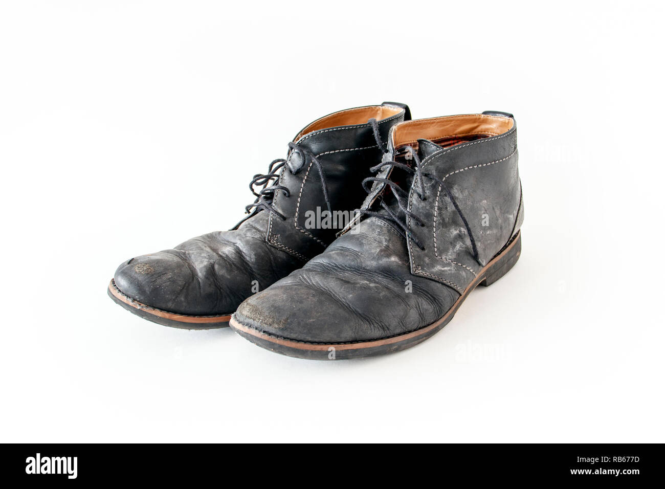 A pair of old tattered black leather lace-up shoes with water stains - Stock Image